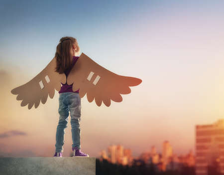 Photo pour Little girl plays outdoors. Child on the background of sunset sky. Kid with the wings of a bird dreams of flying. - image libre de droit