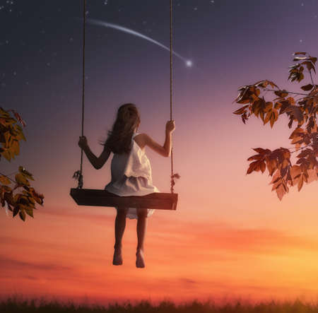 Photo pour Happy child girl on swing in sunset summer. Kid makes a wish by seeing a shooting star. - image libre de droit