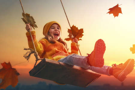 Photo pour Happy child girl on swing in sunset fall. Little kid playing in the autumn on the nature walk. - image libre de droit