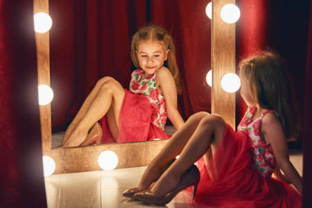 Foto de Cute little fashionista. Happy child girl try on outfits and mom's shoes looking at mirror. - Imagen libre de derechos