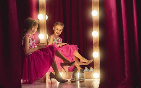 Photo pour Cute little fashionista. Happy child girl try on outfits and mom's shoes looking at mirror. - image libre de droit