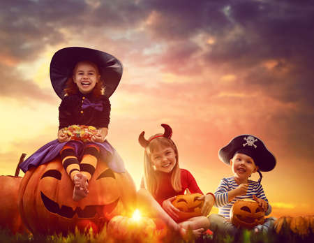 Photo for Happy brother and two sisters on Halloween. Funny kids in carnival costumes outdoors. Cheerful children and pumpkins on sunset background. - Royalty Free Image
