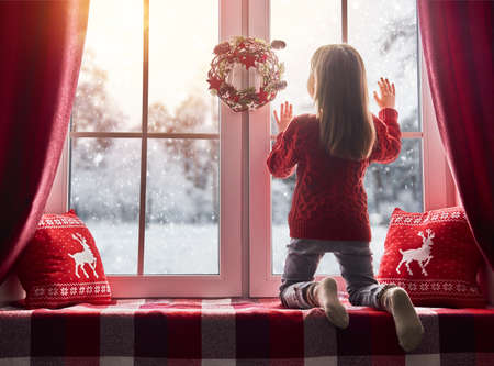 Photo for Merry Christmas and happy holidays! Cute little girl sitting by the window and looking at the winter forest. Room decorated on Christmas. Kid enjoys the snowfall. - Royalty Free Image
