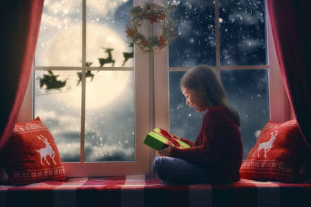Photo for Merry Christmas and happy holidays! Cute little child girl sitting by window and looking at Santa Claus flying in his sleigh against moon sky. Room decorated on Christmas. Kid enjoy the holiday. - Royalty Free Image