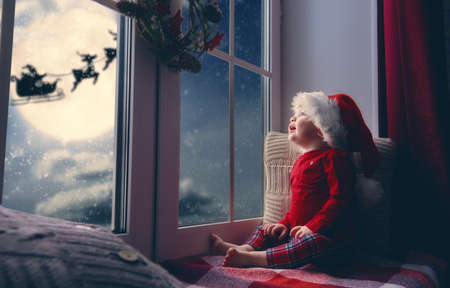 Photo pour Merry Christmas and happy holidays! Cute little child baby girl sitting by window and looking at Santa Claus flying in his sleigh against moon sky. Room decorated on Christmas. Kid enjoy the holiday. - image libre de droit
