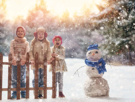 Photo pour Cute children girls and boy playing on a winter walk in nature. Happy kids outdoors. - image libre de droit