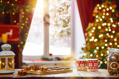 Photo pour Merry Christmas and Happy Holidays. Time of family tea party. Cups of warm tea with Christmas cookies on wooden table. - image libre de droit
