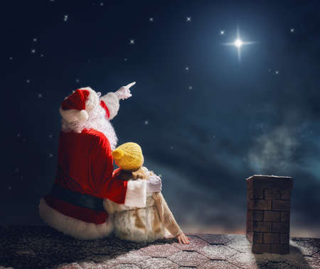Photo for Merry Christmas and happy holidays! Cute little child girl and Santa Claus sitting on the roof and looking at Christmas star. Christmas legend concept. - Royalty Free Image