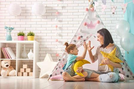 Foto de Happy loving family. Mother and her daughter girl play in children room. Funny mom and lovely child having fun indoors. - Imagen libre de derechos