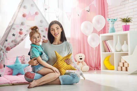 Photo for Happy loving family. Mother and her daughter girl play in children room. Funny mom and lovely child having fun indoors. - Royalty Free Image