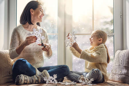 Photo pour Merry Christmas and happy holidays! Happy loving family sitting by the window and making paper snowflakes for decoration windows. Mother and child creating decorations. - image libre de droit