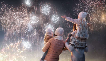 Foto de New Year holiday. Happy family, parents and daughters children girls are watching fireworks. The child sits on the shoulders of his father on snowy winter walk in nature. Holidays winter season. - Imagen libre de derechos