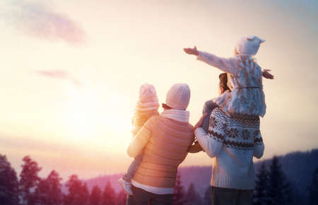 Foto de Happy family at sunset. Father, mother and two children daughters are having fun and playing on snowy winter walk in nature. The child sits on the shoulders of his father. Frost winter season. - Imagen libre de derechos