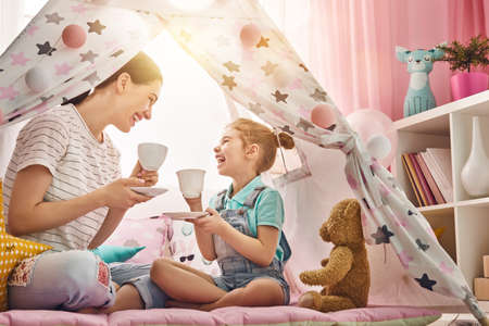 Photo for Happy loving family. Mother and her daughter girl play tea-party and drink tea from cups in children room. Funny mom and lovely child having fun indoors. - Royalty Free Image