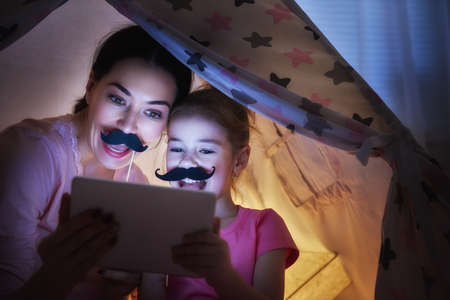 Photo pour Happy loving family. Young mother and her daughter girl play in children room at the bedtime. Funny mom and lovely child are having fun with tablet. - image libre de droit
