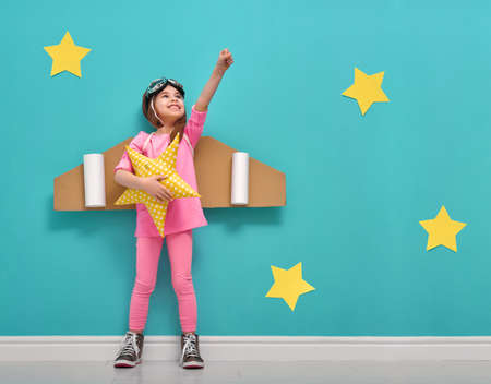Foto de Little child girl in an astronaut costume is playing and dreaming of becoming a spaceman. Portrait of funny kid on a background of bright blue wall with yellow stars. - Imagen libre de derechos