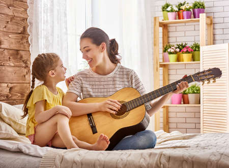 Photo for Happy family. Mother and daughter together. Adult woman playing guitar for child girl. - Royalty Free Image