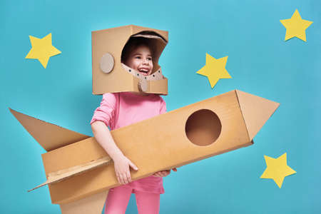 Foto de Child girl in an astronaut costume with toy rocket playing and dreaming of becoming a spacemen. Portrait of funny kid on a background of bright blue wall with yellow stars. - Imagen libre de derechos
