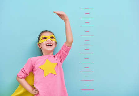 Foto de Little child plays superhero. Kid measures the growth on the background of bright blue wall. Girl power concept. Yellow, pink and  turquoise colors. - Imagen libre de derechos