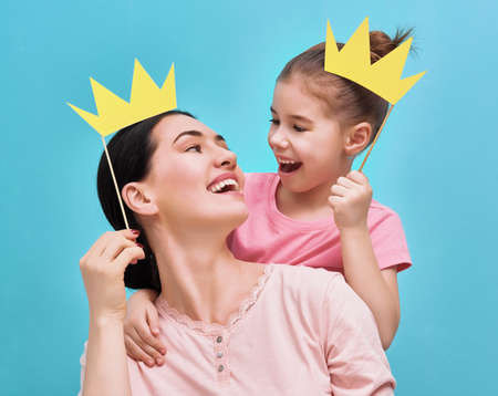 Photo for Funny family on a background of bright blue wall. Mother and her daughter girl with a paper accessories. Mom and child are holding paper crown on stick. - Royalty Free Image