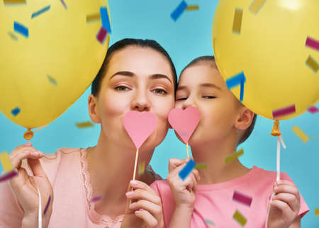 Photo for Funny family on a background of bright blue wall. Mother and her daughter girl are having fun with balloons and confetti. Yellow, pink and turquoise colors. - Royalty Free Image