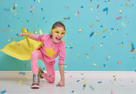 Foto de Little child plays superhero. Kid on the background of bright blue wall. Girl is throwing confetti. Yellow, pink and  turquoise colors. - Imagen libre de derechos