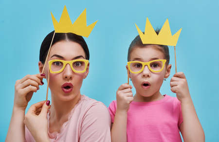 Photo pour Funny family on a background of bright blue wall. Mother and her daughter girl with a paper accessories. Mom and child are holding crowns glasses and on stick. - image libre de droit