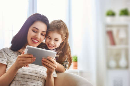 Foto de Happy loving family. Young mother and her daughter girl play in kids room. Funny mom and lovely child are having fun with tablet. - Imagen libre de derechos