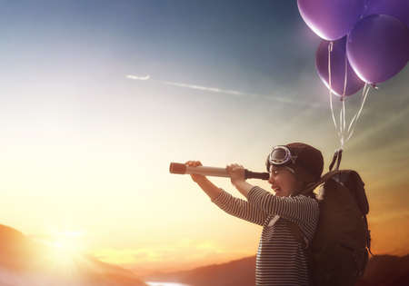 Photo pour Dreams of travel! Child flying on balloons against the backdrop of a sunset. - image libre de droit