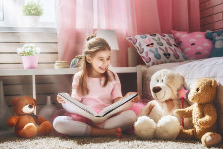 Photo for Cute little kid girl is reading a book at home. Funny lovely child having fun in kids room. - Royalty Free Image