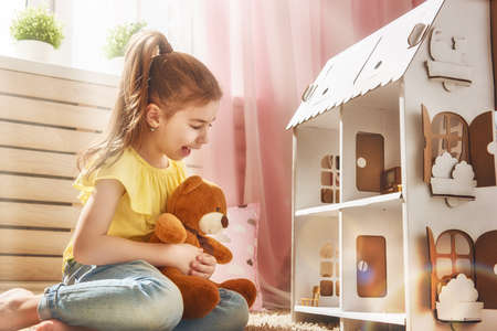 Photo pour Happy girl plays with doll house and teddy bear at home. Funny lovely child is having fun in kids room. - image libre de droit