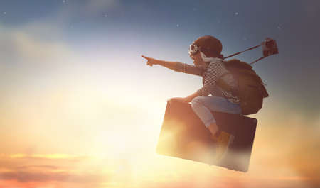 Photo pour Dreams of travel! Child flying on a suitcase against the backdrop of sunset. - image libre de droit