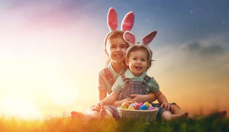 Photo for Two cute little children wearing bunny ears. Girls are sitting on the lawn. Kids with Easter eggs in the rays of the setting sun. - Royalty Free Image