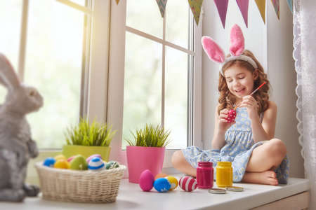 Photo for Cute little child wearing bunny ears. Girl sitting on the window. Kid is painting eggs. - Royalty Free Image