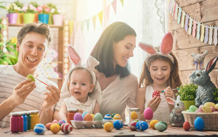 Photo for Mother, father and daughters are painting eggs. Happy family are preparing for Easter. Cute little child girl wearing bunny ears. - Royalty Free Image