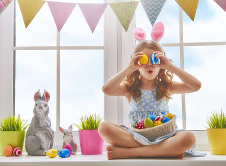 Photo pour Cute little child wearing bunny ears. Girl sitting on the window with painting eggs. - image libre de droit