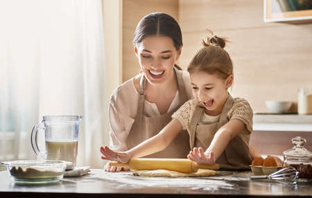 Photo for Happy loving family are preparing bakery together. Mother and child daughter girl are cooking cookies and having fun in the kitchen. Homemade food and little helper. - Royalty Free Image