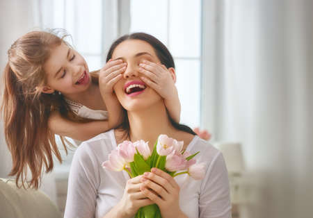 Photo pour Happy mother's day! Child daughter congratulates mom and gives her flowers tulips. Mum and girl smiling and hugging. Family holiday and togetherness. - image libre de droit