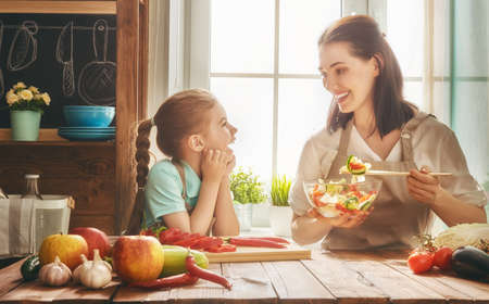 Photo pour Healthy food at home. Happy family in the kitchen. Mother and child daughter are preparing the vegetables and fruit. - image libre de droit