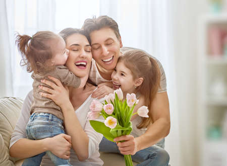Photo for Happy mother's day! Two children daughters with dad congratulate mom and give her flowers tulips. Mum and girls smiling and hugging. Family holiday and togetherness. - Royalty Free Image