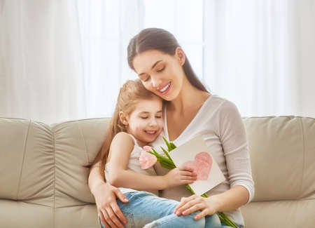 Photo pour Happy mother's day! Child daughter congratulates mom and gives her flowers tulips and postcard. Mum and girl smiling and hugging. Family holiday and togetherness. - image libre de droit
