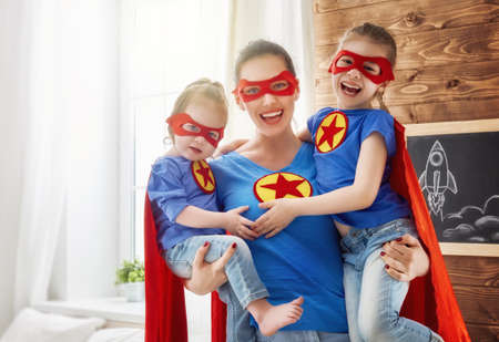 Photo pour Mother and her children playing together. Girls and mom in Superhero costumes. Mum and kids having fun, smiling and hugging. Family holiday and togetherness. - image libre de droit