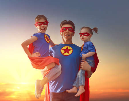 Photo for Happy loving family. Dad and his daughters are playing outdoors. Daddy and his children girls in an Superhero's costumes. Concept of Father's day. - Royalty Free Image