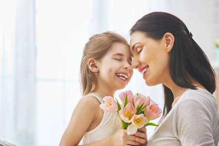 Photo for Happy mother's day! Child daughter congratulates mom and gives her flowers tulips. Mum and girl smiling and hugging. Family holiday and togetherness. - Royalty Free Image