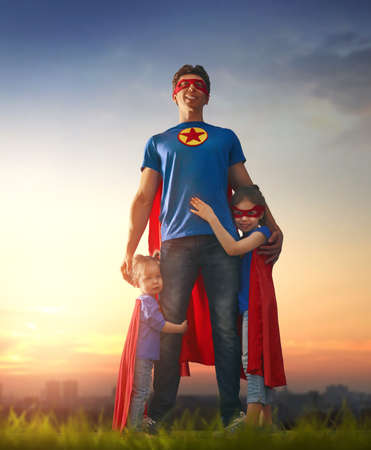 Photo pour Happy loving family. Dad and his daughters are playing outdoors. Daddy and his children girls in an Superhero's costumes. Concept of Father's day. - image libre de droit