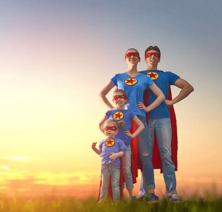 Foto de Mother, father and their daughters are playing outdoors. Mommy, daddy and children girls in an Superhero's costumes. Concept of super family. - Imagen libre de derechos