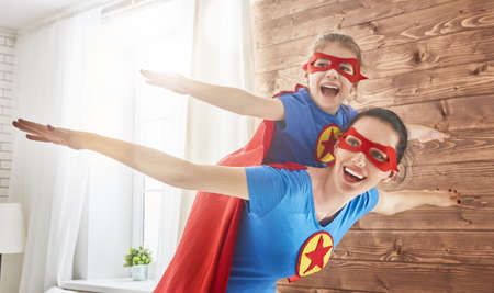Photo pour Mother and her child playing together. Girl and mom in Superhero costume. Mum and kid having fun, smiling and hugging. Family holiday and togetherness. - image libre de droit