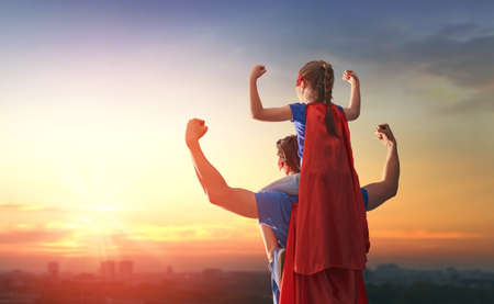 Foto de Happy loving family. Dad and his daughter playing outdoors. Daddy and child girl in an Superhero's costumes. Concept of Father's day. - Imagen libre de derechos