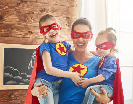 Photo for Mother and her children playing together. Girls and mom in Superhero costumes. Mum and kids having fun, smiling and hugging. Family holiday and togetherness. - Royalty Free Image