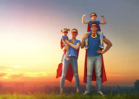 Photo pour Mother, father and their daughters are playing outdoors. Mommy, daddy and children girls in an Superhero's costumes. Concept of super family. - image libre de droit